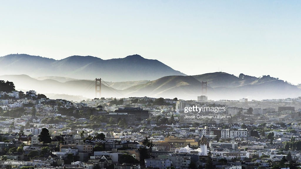 Cityscape By Mountains Against Clear Sky During Foggy Weather : Stock Photo