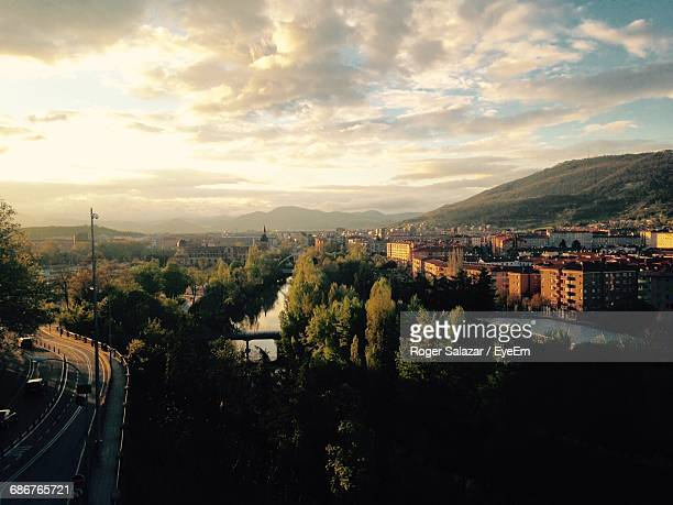 cityscape by mountains against cloudy sky - pamplona stock photos and pictures