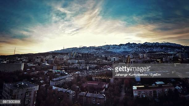 Cityscape By Mountains Against Sky During Sunset