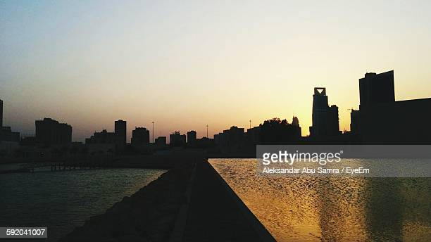 cityscape by river against clear sky at sunset - manama stock pictures, royalty-free photos & images