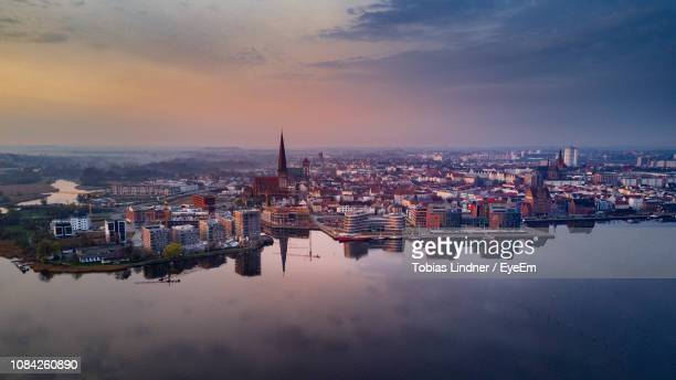 cityscape by river against sky during sunset - rostock stock pictures, royalty-free photos & images