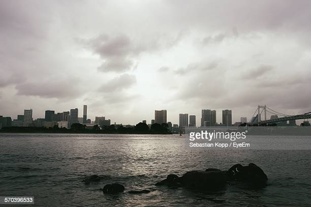 Cityscape By Sea Against Cloudy Sky