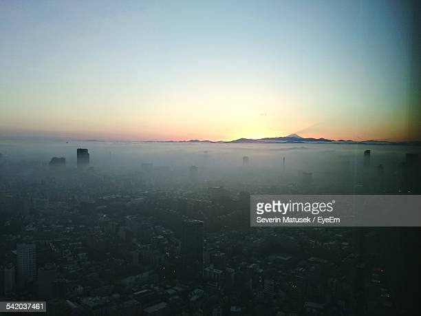 Cityscape Covered With Foggy Weather Against Clear Sky During Sunrise