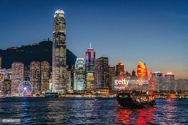 cityscape hong kong and junkboat at twilight - hong kong stock pictures, royalty-free photos & images