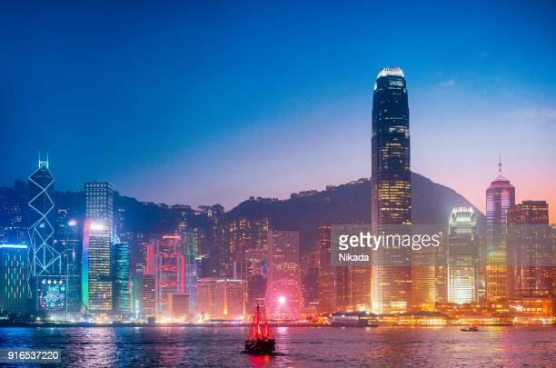 paysage urbain hong kong avec junkboat au crépuscule - hong kong photos et images de collection