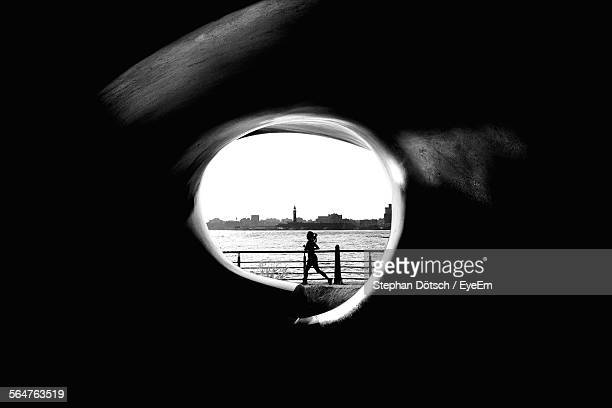 cityscape next to silhouetted woman seen through hole in stone wall - wall building feature stock photos and pictures
