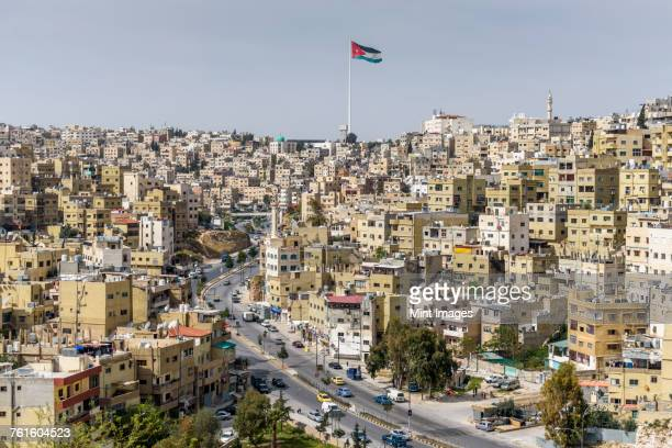 cityscape of jerash in the north of jordan, with jordanian flag flying. - jordan stock pictures, royalty-free photos & images