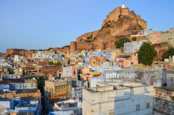 cityscape of jodhpur with traditional indigo blue and white painted houses and the 15th century mehrangarh fortress on the hilltop. - jodhpur stock pictures, royalty-free photos & images