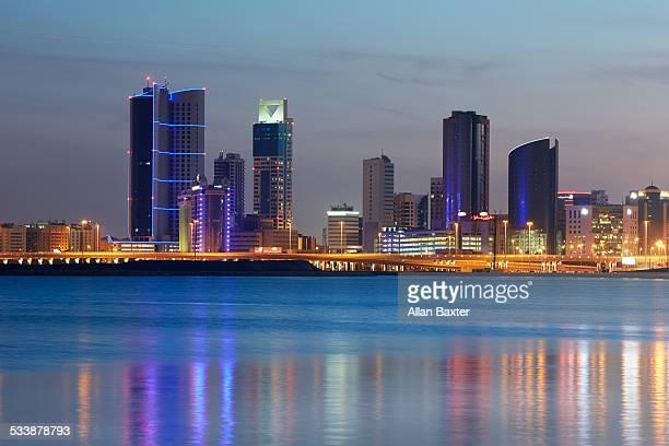 cityscape of manama illuminated at dusk - manama stock pictures, royalty-free photos & images