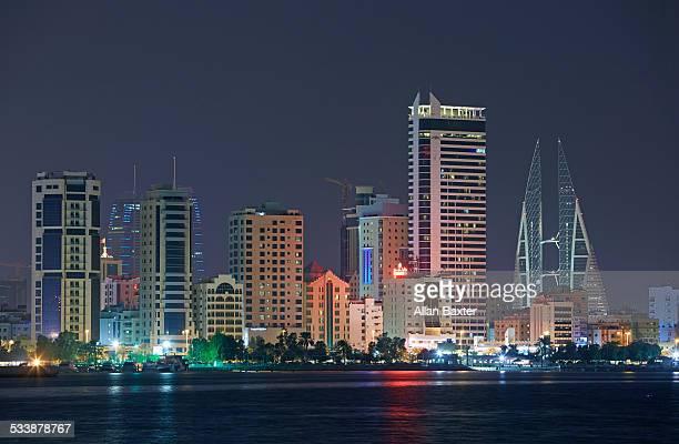 cityscape of manama illuminated at night - manama stock pictures, royalty-free photos & images