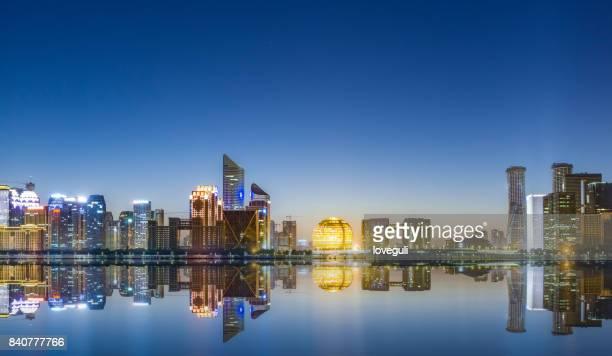 cityscape of modern city near river at dawn