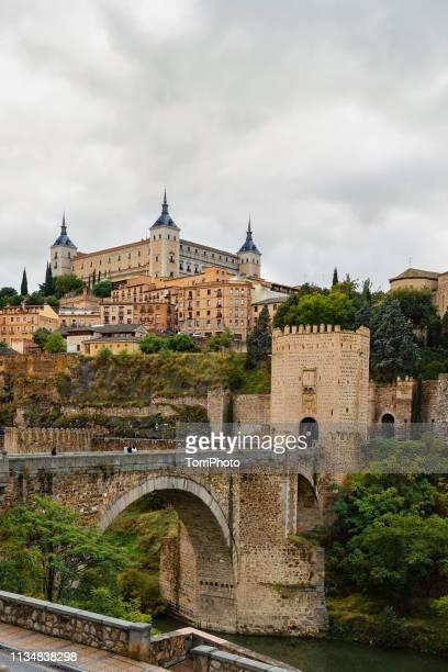 Cityscape of old Spain town Toledo with Alcazar castle and Alcantara Bridge