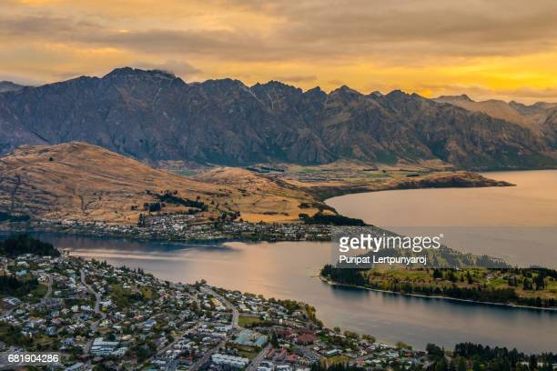 Cityscape of Queenstown at night with The Remarkables in the background from viewpoint at Queenstown Skyline, New Zealand