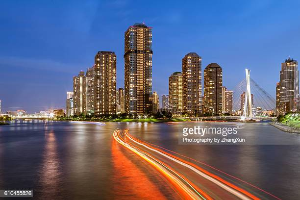 Cityscape of Tsukishima in Tokyo with houseboat light trails after dark