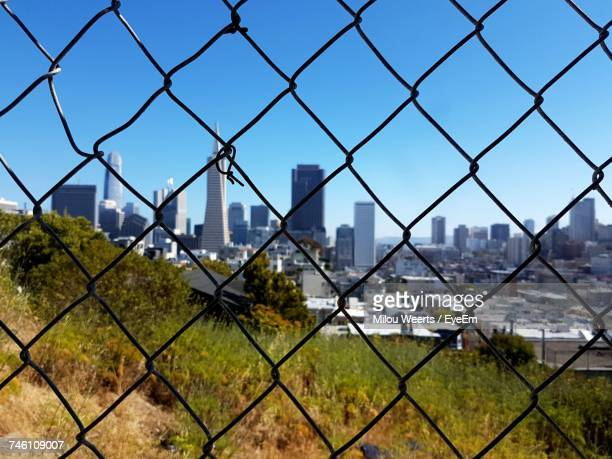 Cityscape Seen Through Chainlink Fence