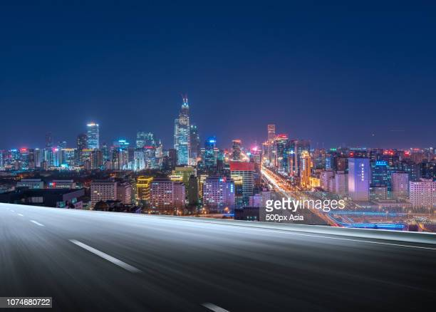 cityscape with illuminated skyscrapers and empty road, beijing, china - image stockfoto's en -beelden