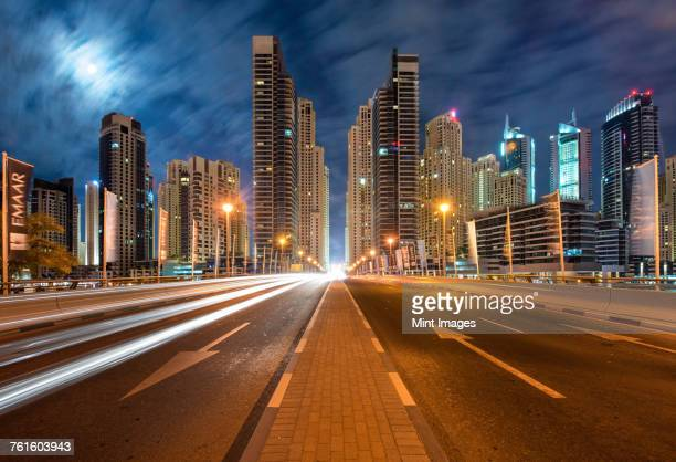 Cityscape with illuminated skyscrapers in Dubai, United Arab Emirates at dusk, highway in foreground.