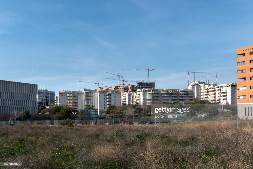 Cityscape with new buildings and cranes with empty land in the foreground : Foto de stock