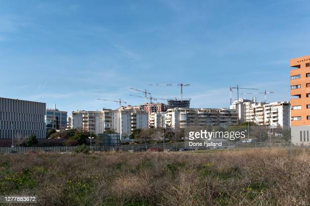 cityscape with new buildings and cranes with empty land in the foreground - dorte fjalland fotografías e imágenes de stock