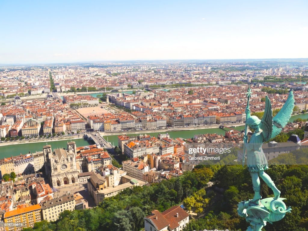 Cityscape with statue of angel, Lyon, France : Stock Photo