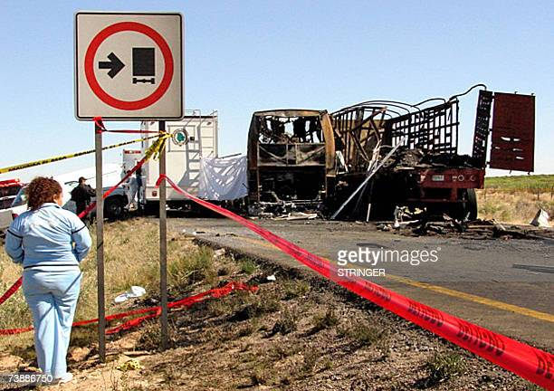 A woman looks at firefighters and forensic doctors as they rescue bodies from a burnt bus in the ChihuahuaJuarez road northern Mexico 14 April 2007...