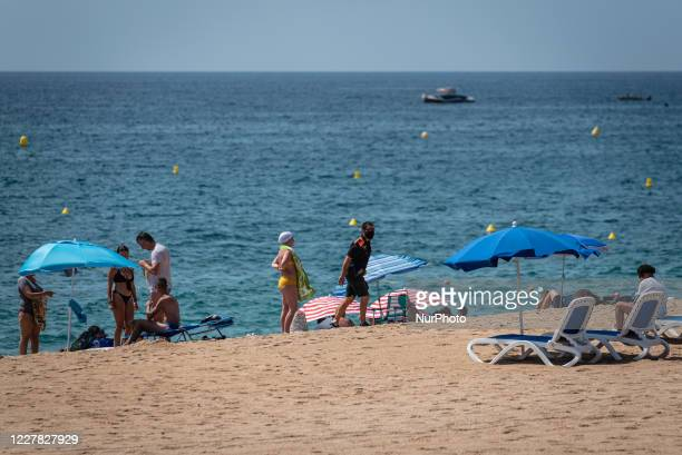 Civic agent is checking that people is following Covid19 rules in Lloret de Mar beach Summer season in Lloret de Mar is being bad after the advices...