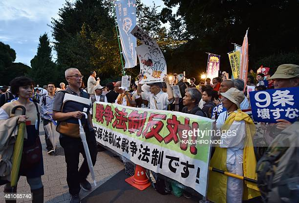 Civic group members stage an anti-government rally outside the National Diet in Tokyo on July 17, 2015 to protest against the controversial security...