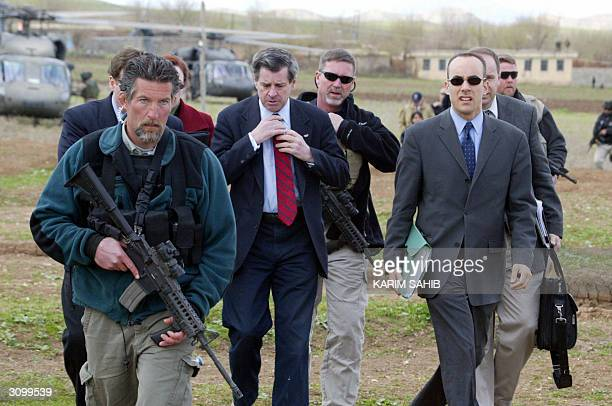 US civil administrator in Iraq Paul Bremer is flanked by bodyguards upon his arrival by helicopter in the Kurdish Iraqi town of Halabja near the...