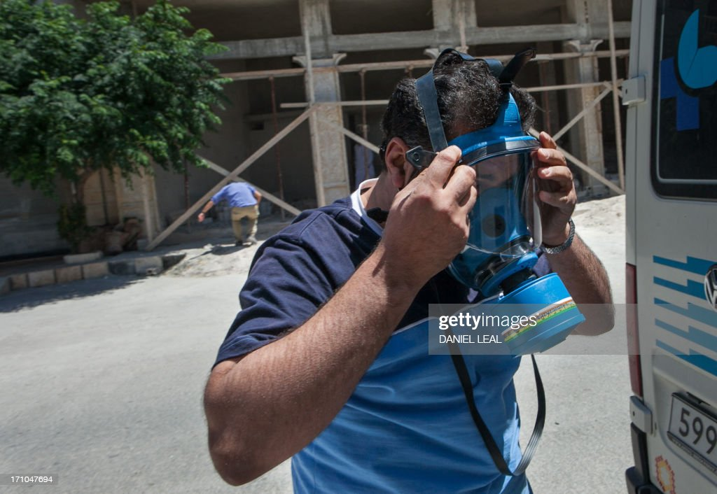 A civil ambulance driver puts on a gas mask after reports of upcoming chemicals atticks in the area during clashes in the village of Al-Rami, near the town of Ariha, in the northwestern province of Idlib on June 21, 2013. Rebels and activists have been reporting heavy clashes between rebels and government forces in Idlib province as government troops are trying to take control of the highway that leads to the neighbouring Latakia province. AFP PHOTO / DANIEL LEAL-OLIVAS / AFP PHOTO / Daniel LEAL