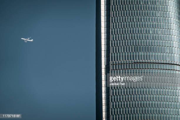 civil aviation aircraft flying in blue sky - wuhan city stock photos and pictures