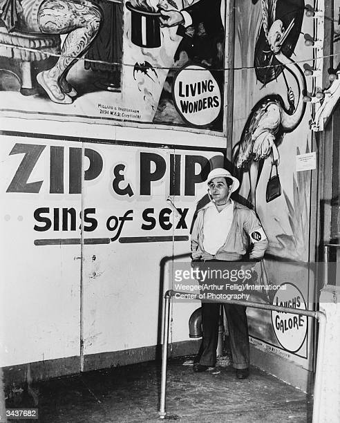 Civil Defence Air warden stands outside a sideshow in New York City showing 'Living Wonders Zip and Pip Sins of Sex' Photo by Weegee/International...