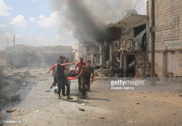 Civil defence crew members carry an injured person away from the scene after airstrikes by Assad Regime hit the deescalation zone of Maar Shurin...