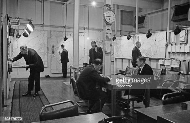 Civil Defence employees study maps and answer telephones in the main control room at Air Raid Precautions headquarters in Liverpool, England during...