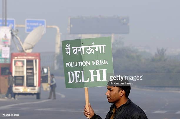 Civil Defence personnel holds a placard as he stands at a traffic intersection on the first day of Delhi's OddEven Vehicle Plan on January 1 2016 in...