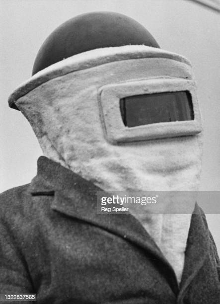 Civil defence roof firewatcher of the Air Raid Precaution wears an asbestos fire protection hood and helmet as protection against incendiary bombs on...
