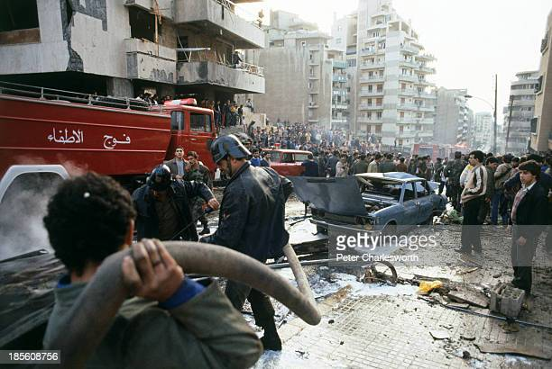 Civil defence volunteers, firemen and passers-by try to help rescue victims and put out fires caused by a massive car bomb, detonated in a main...