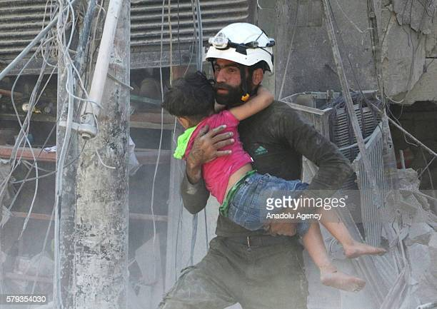 A civil defence worker carries a child through rubble as civil defense team members and the citizens try to rescue people who were trapped under the...