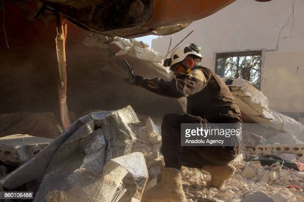 A civil defense member carries out search and rescue work on the debris of a building after Assad regime's airstrikes hit the town of Khan Shaykhun...