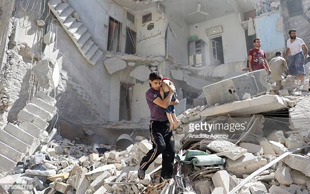 A civil defense member rescues a boy from wreckage after a barrel bomb attack staged by Syrian army in the oppositioncontrolled Mashhad district of...