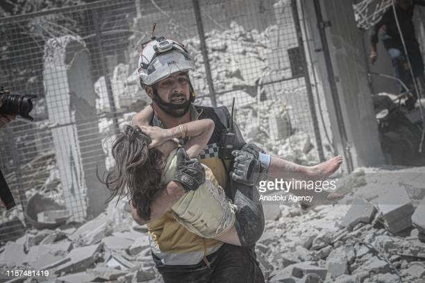 A civil defense member saves a baby under the debris as search and rescue works are being carried out at the site after airstrikes of Russia and...