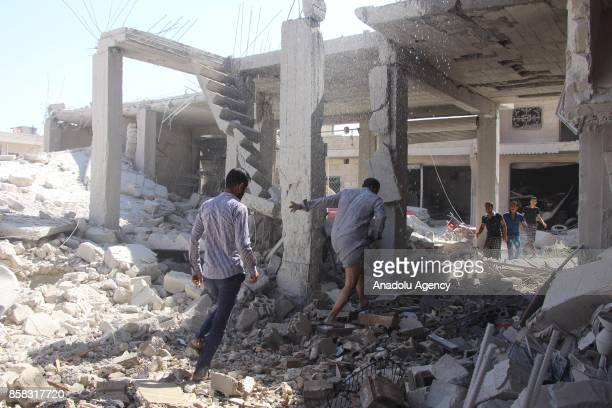 Civil defense members and citizens carry out search and rescue works on the debris of a building after Assad regime's airstrikes hit the town of Khan...