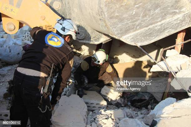 Civil defense members carry out search and rescue work on the debris of a building after Assad regime's airstrikes hit the town of Khan Shaykhun in...