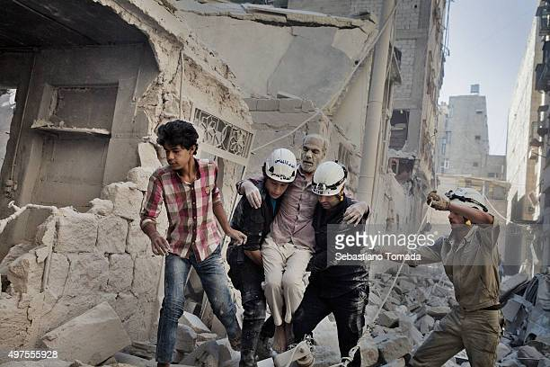 Civil Defense members rescue a man who had been trapped inside his home after a barrel bomb collapsed it June 20 2014