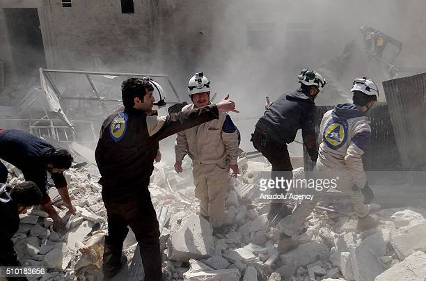 Civil defense members try to rescue victims from the wreckage after the Russian airstrikes targeted residential areas in opposition controlled...