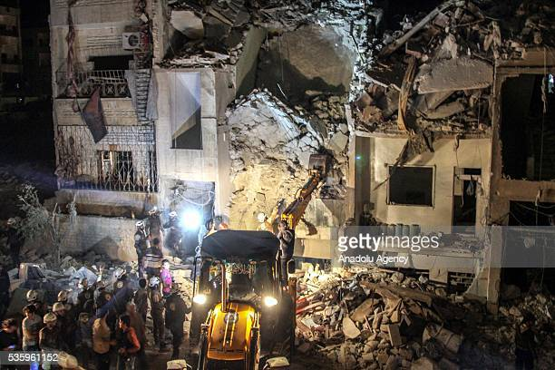 Civil defense members try to rescue victims from the wreckage of National Hospital after the Russian airstrikes targeted Idlib Syria on May 31 2016