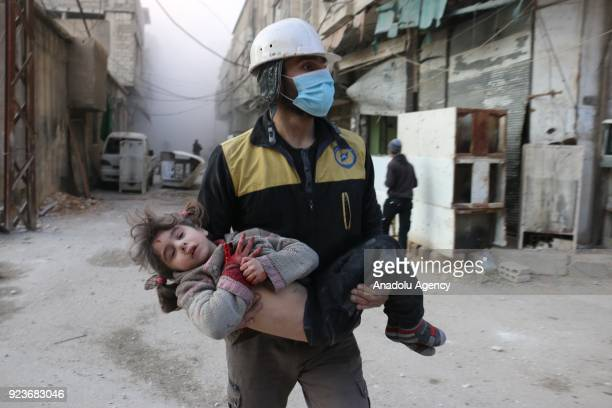 Civil defense team member carries a wounded baby rescued from a wreckage after Assad regime forces carried out airstrikes over the deescalation zone...