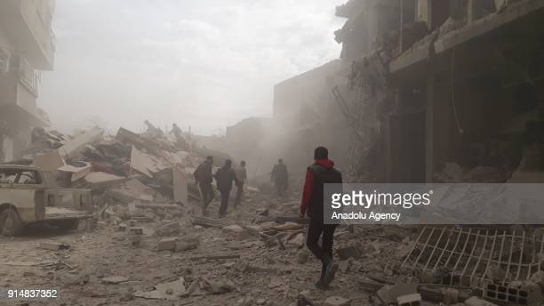 Civil defense team members and citizens carry out search and rescue works after war planes belonging to Assad regime carried out airstrikes over...