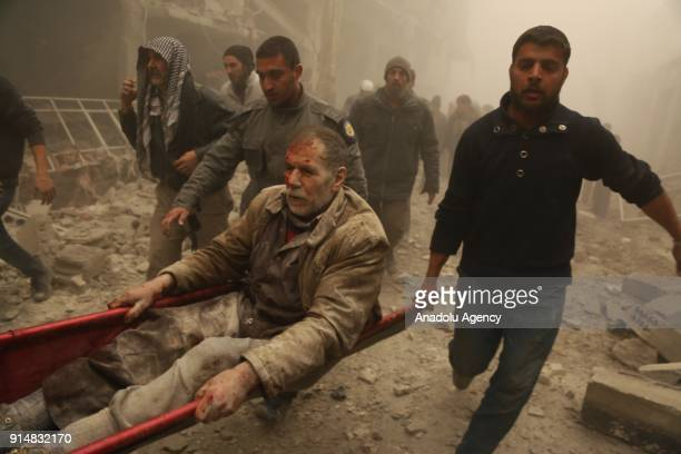 Civil defense team members and civillians rescue a wounded man from debris of a building after war planes belonging to Assad regime carried out...