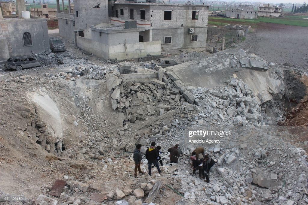 Civil defense team members and people try to rescue people who were trapped under the debris of a Mosque after warcrafts belonging to USA airforces carried out airstrikes during night prayer in Al-Jineh village of Atarib district in Aleppo, Syria on March 17, 2017.