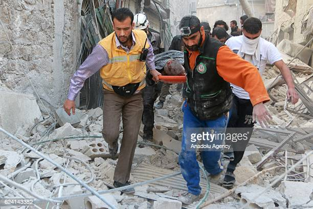 Civil defense team members carry a wounded man on the debris buildings after the war crafts belonging to the Assad Regime carried out airstrikes on...
